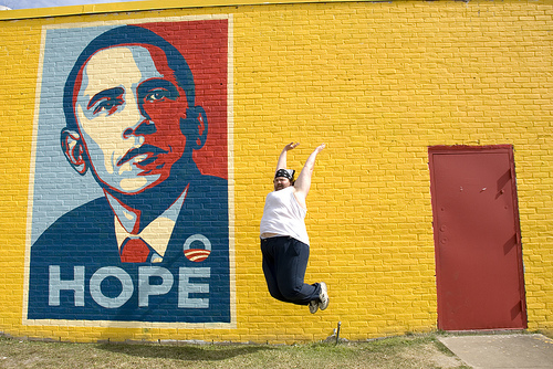 Man leaping in front of Obama mural