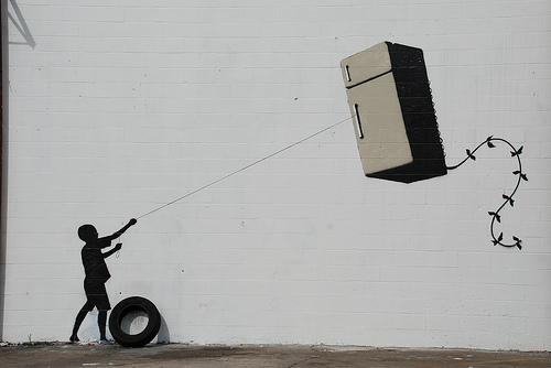 Stencil art of child flying a fridge-kite